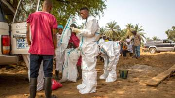 Burial teams in Sierra Leone put on protective overalls during an Ebola outbreak
