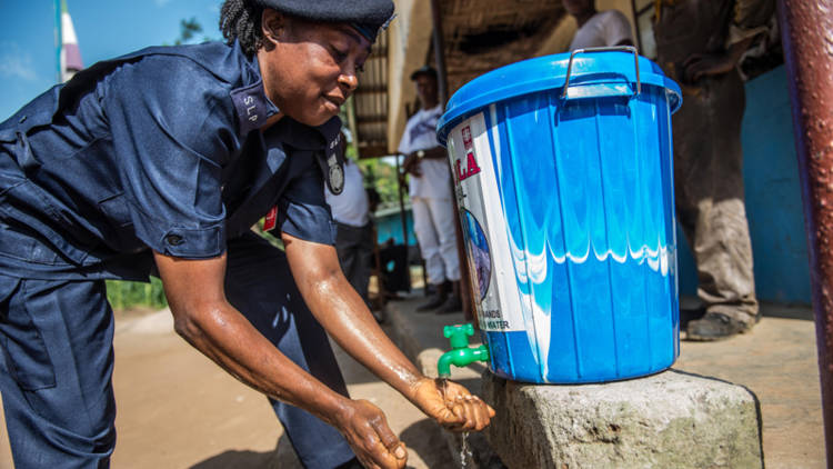 "A police officer washes her hands in an ""ebola bucket"" provided by CAFOD partner Caritas in Sierra Leone. Photo: Tommy Trenchard for Caritas"