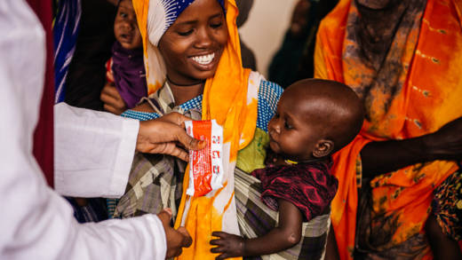 Adeego Adan Hussein is assisted by hospital staff in feeding her daughter, Deeqa Ibrahim, with Plumpy Sup