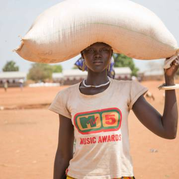 Liapwel Mabor carries a sack of sorghum  after receiving the food at the distribution center in Billing Payam in Yirol East.