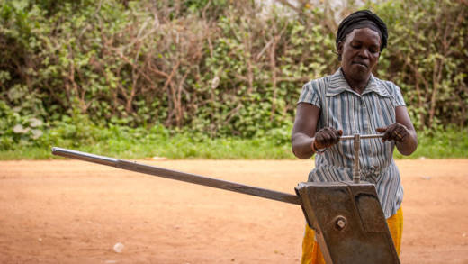 Teko Anna, Proscovia's mother, mending their local water pump, after training from CAFOD partners.