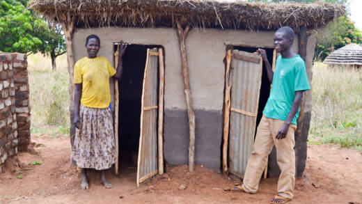 Samuel and Monica stand proudly outside their new toilets