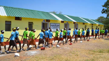 Schoolchildren walk past a new block of toilets in Zimbabwe