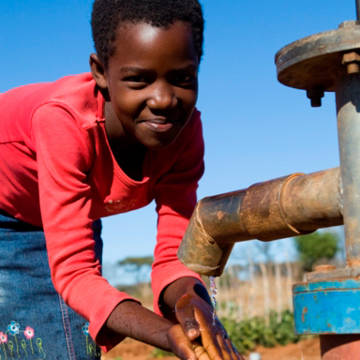 Zimi pumping water. CAFOD mended two community boreholes which provide water all year round for Zimi's family.