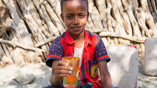 Abdul, a boy in Ethiopia, holding a glass of water