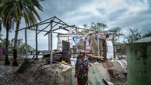 A woman stands outside her home, which has been destroyed by Cyclone Amphan as it tore through Bangladesh.