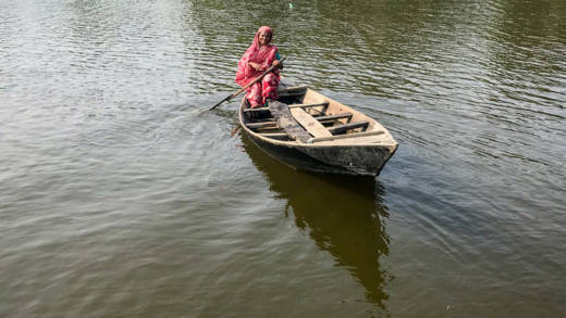 Mahinur in a boat crossing the river that separates her home from the rest of the village.