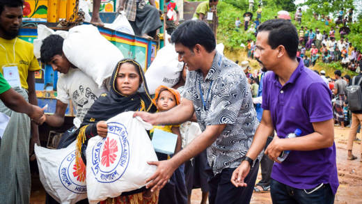 A woman with a baby receives an aid package from CAFOD's partners in Bangladesh.