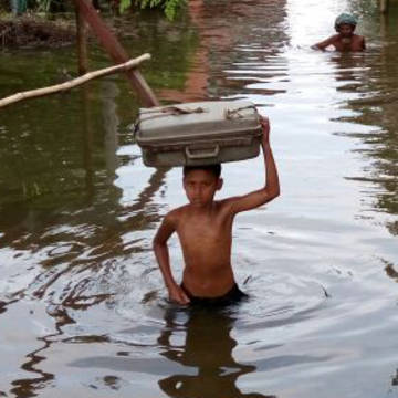 A boy holds up a suitcase from the floodwaters