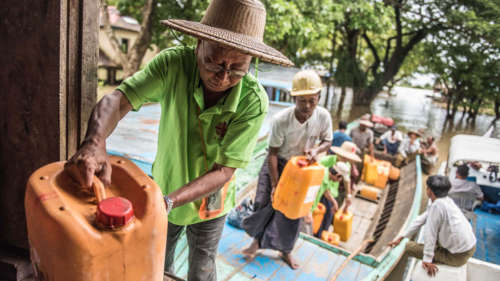 A CAFOD partner delivers aid by boat during this year's floods in Myanmar