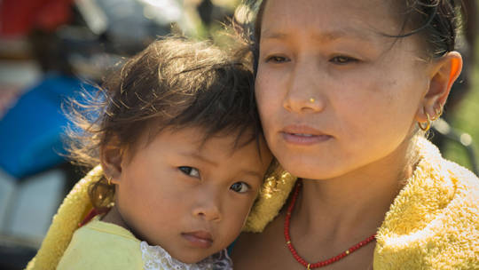 Kue Maya and her two-year-old daughter at a shelter kit distribution by CAFOD partners.  Photo by Jake Lyell for Catholic Relief Services
