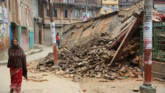 A woman walks past collapsed buildings in the town centre. Photo: Caritas Nepal