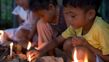 Children in the Philippines lighting memorial candles