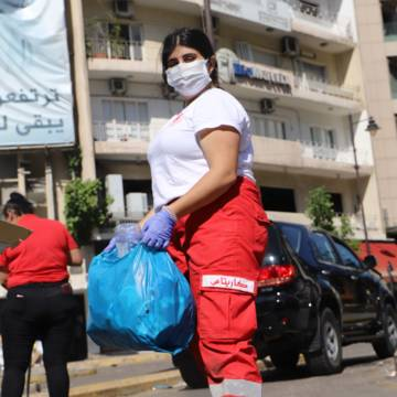 A member of CAFOD partner Caritas Lebanon helps to clean up the streets after the Beirut explosion.