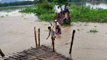 People crossing a broken bridge after severe flooding