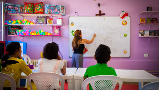 A teacher writes on a classroom whiteboard in front of a table of three children
