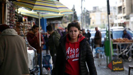 Aya, 24, is one of over one million refugees who is living in Lebanon. She is walking down a street in Tripoli.