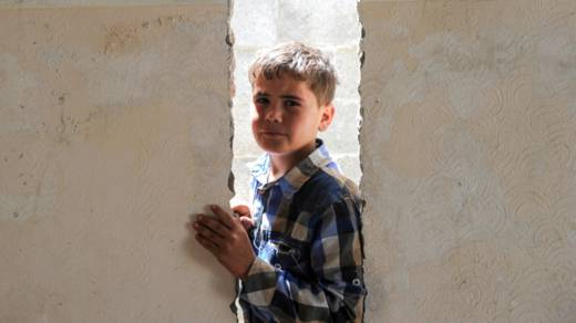 Mohammed, age 11, stands inside his destroyed home in Gaza