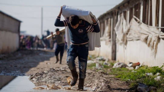 A Syrian boy carrying blankets