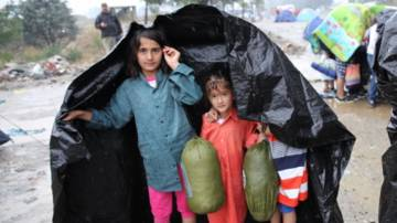 Refugee children from Syria take shelter from the rain