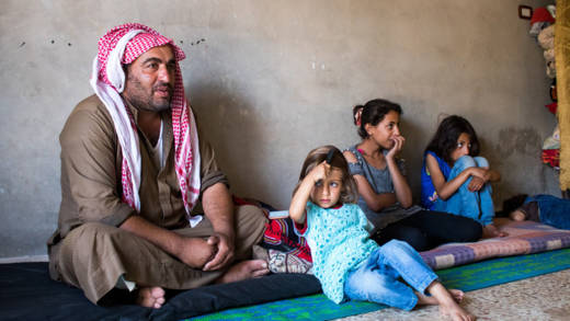 A father sits on the floor alongside three of his children
