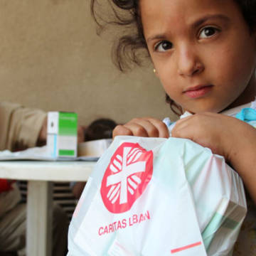 A Syrian refugee child holds free medicine given to her by a mobile clinic run by CAFOD partner Caritas Lebanon.