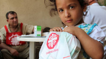 A Syrian refugee child holds free medicine given to her by a mobile clinic run by our partner Caritas Lebanon.