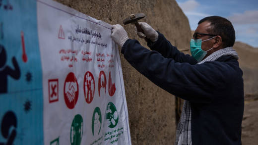 Man attaching coronavirus poster to wall in Afghanistan