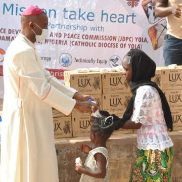 Bishop Stephen Dami Mamza wears a face mask to give a coronavirus hygiene kit to a refugee family in Nigeria