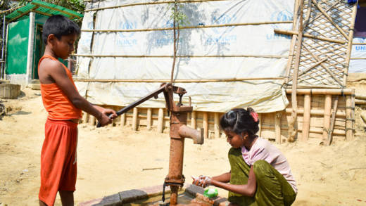 A little girl washes her hands with soap at a water pump