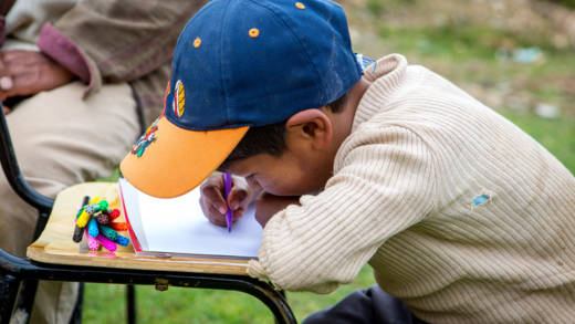 A boy wearing a baseball cap outside drawing a picture.