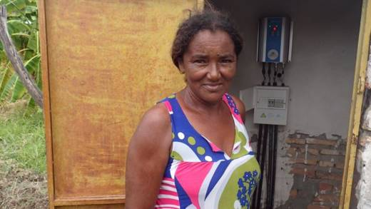 Maria proudly stands next to the electricity meter in her community.