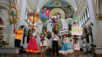 Children hold up placards ahead of the Amazon Synod
