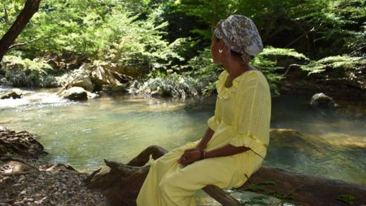 A woman sitting on the branch of a tree next to a stream