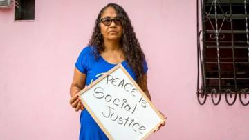"""A woman holds a placard saying """"peace is social justice"""""""