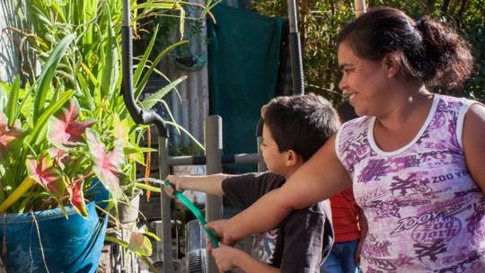 Diego watering plants with his mother in El Salvador