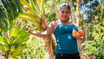 Edelmira with cashew nuts and bananas on her farm in El Salvador