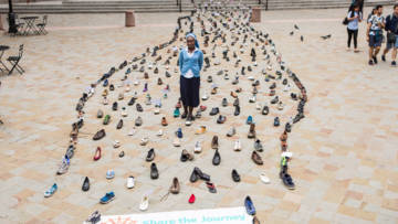Sister Clara - a CAFOD volunteer - walks among 400 pairs of shoes for the Share the Journey campaign.