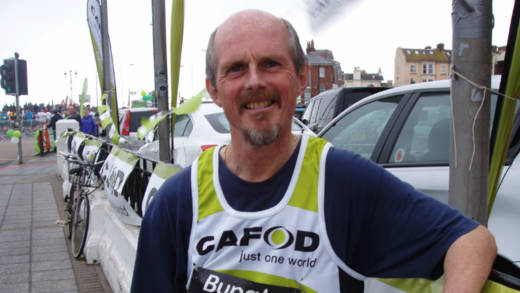 Kevin Lawler running the Great South Run for CAFOD for the tenth time. Here he is standing next to CAFOD banners with a CAFOD t-shirt after finishing the race.