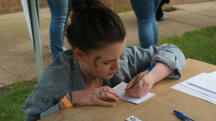A young adults signs a refugee action card at  Brightlights festival