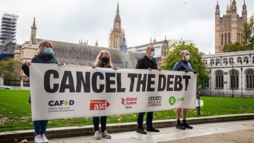 Four campaigners hold a long banner that reads 'Cancel the debt'