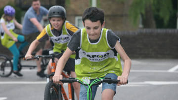 Two young people riding bicycles, behind them a tandem is turning