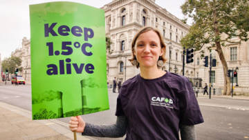 """CAFOD campaigner holding a placard reading """"Keep 1.5 alive"""""""