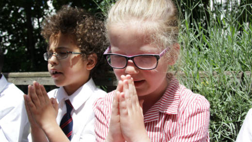Children from Sacred Heart Primary School praying outdoors.