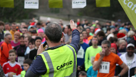 CAFOD volunteer speaks to runners at the start of the 2015 Bollington fun Run
