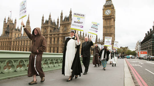 Monks and nuns march over Westminster Bridge campaigning for an end to hunger