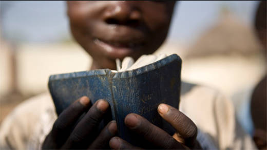 a boy brings his bible into a CAFOD funded clinic i nNigeria  so that he can read to his sick mother