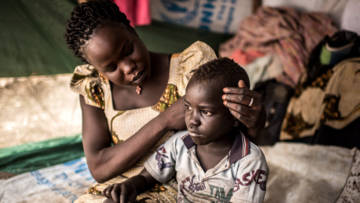 Viola Tabo from South Sudan, with her son, in their tent in Bidi Bidi settlement, Uganda.