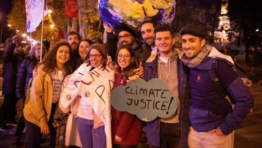 """Activists at COP25 holding a placard reading """"climate justice"""""""