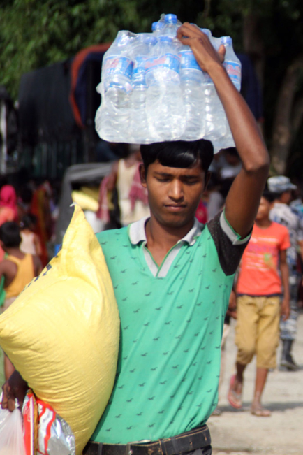 A man carries aid supplies, including clean water, after floods hit south Asia